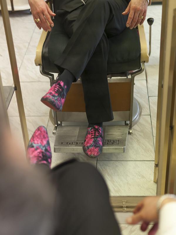 Hombre sentado en silla de peluquería con zapatos de flores