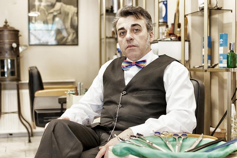 Hombre clásico con pajarita de colores en peluquería vintage
