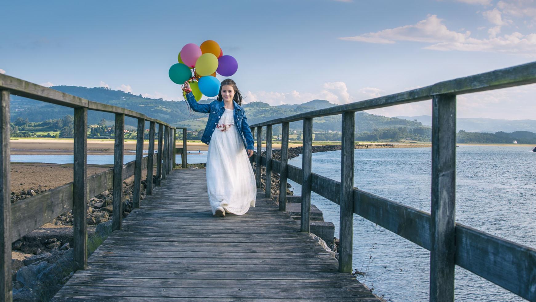 Niña vestida de comunión con globos de colores